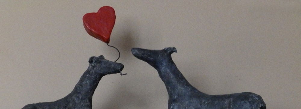 Two Greyhounds, head-to-head, with heart-shaped balloon